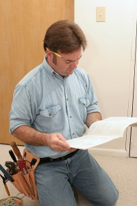 An electrician reading the manual to a ceiling fan prior to installing it.