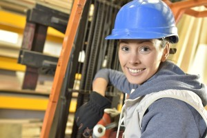 Female factory technician using forklift