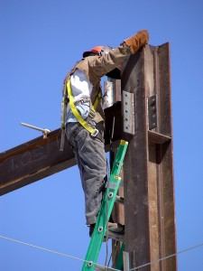 Construction worker climbing to the top of a steel beam high rise building project