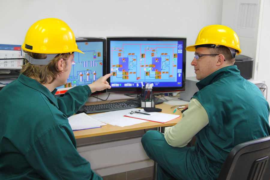 Industrial workers in front of computer in control room