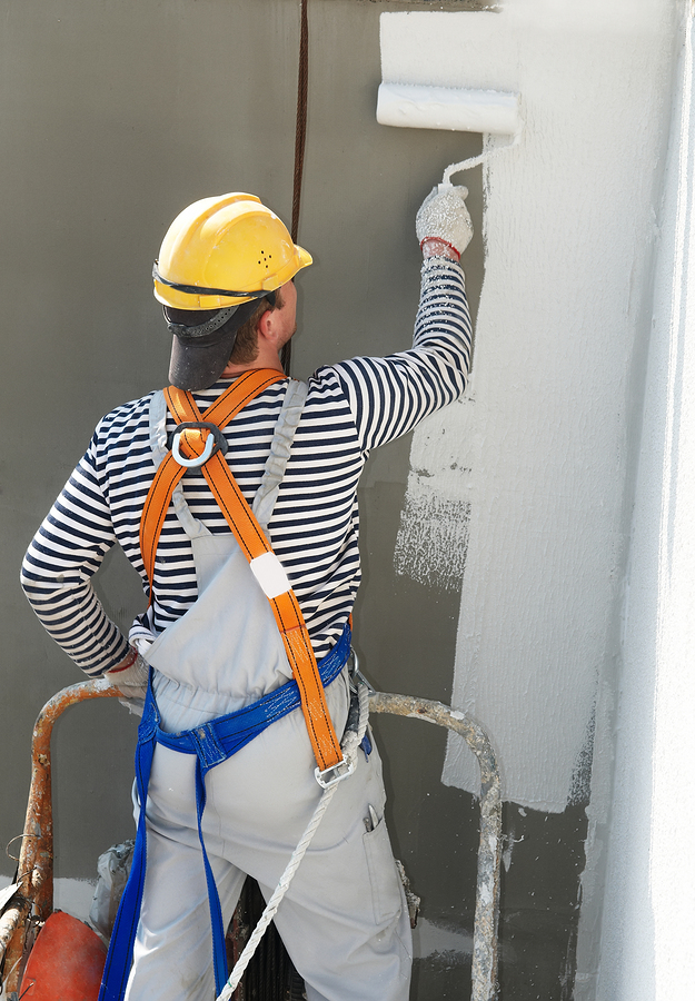 builder worker painting facade of high-rise building wearing personal protective equipment to prevent a fall