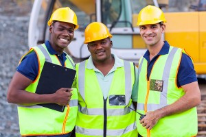 portrait of three smiling construction workers wearing safety gear on the job