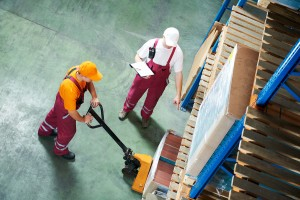 Warehouse supervisor instructing worker on use of fork pallet stacker equipment